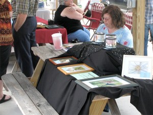 C. Lynn Johnson uses her booth time to paint
